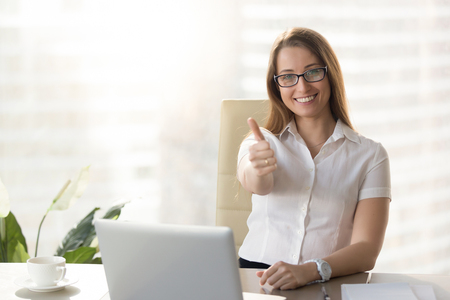 Attractive businesswoman looking at camera, showing thumbs up at workplace, pretty happy manager raising finger sitting at office desk with laptop, likes her job, acceptance approval sign, good idea Stok Fotoğraf