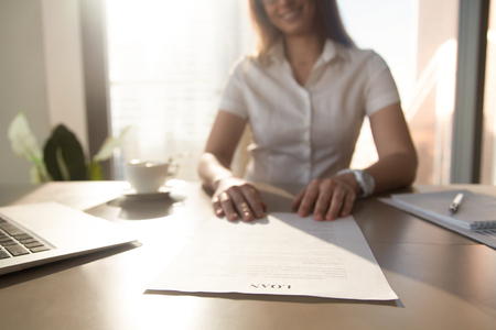 Bank worker offering to read terms of business loan agreement for home purchase, female financial advisor consulting client about commercial credit, mortgage contract, focus on document, close up Stock Photo