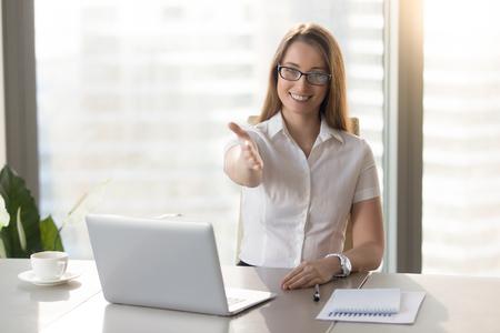 Beleefd vriendelijke zakenvrouw uitbreiding hand op camera, lachende vrouw aanbieden van handdruk tijdens de vergadering op de werkplek op kantoor, open voor samenwerking, groet partner, verwelkomen op sollicitatiegesprek Stockfoto
