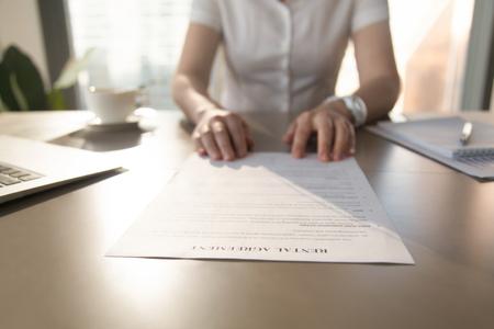 Makelaar biedt huurovereenkomst voor huurder voor huur huis appartement, makelaar geeft woninghuur document aan huurder, stelt voor contract te ondertekenen, focus op papiervoorwaarden, close-up