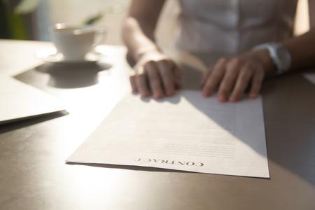 Close up van contract op bureau, zakenvrouw leest contractuele voorwaarden voor het maken van deal tijdens de vergadering op de werkplek, vrouwelijke handen op geschreven document, vrouw herziening overeenkomst, focus op officieel papier