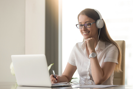 Smiling happy businesswoman in headphones sits at desk, looks at laptop screen, making notes, participating in self-improvement webinar, having fun on internet, communicating online by video call