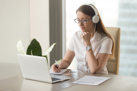 Focused attentive woman in headphones sits at desk with laptop, looks at screen, makes notes, learns foreign language in internet, online study course, self-education on web, consults client by video Banque d'images