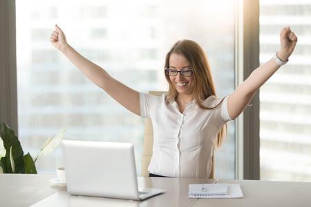 Opgewonden lachende zakenvrouw vieren zakelijk succes op de werkplek, het verhogen van de handen kijken naar laptop scherm, gelukkig voelen over grote overwinning, goed nieuws online, positief resultaat, geslaagd examen, kreeg baan Stockfoto