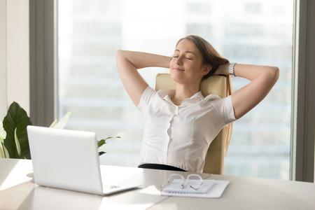 Ruhige lächelnde Geschäftsfrau, die an den bequemen Bürostuhlhänden hinter Kopf, die glückliche Frau stillsteht, die im Büro zufrieden gestellt wird, das nach Arbeit erledigt wird und genießt Bruch mit den geschlossenen Augen, Seelenruhe, kein Druck Standard-Bild