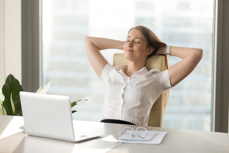 Calm smiling businesswoman relaxing at comfortable office chair hands behind head, happy woman resting in office satisfied after work done, enjoying break with eyes closed, peace of mind, no stress Foto de archivo