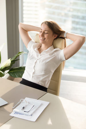 Positive smiling woman relaxing in office chair, happy businesswoman enjoys break, gets inspiration while meditating at workplace, feels relaxed at work desk by closing eyes, holds hands behind head