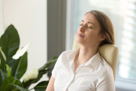 Calm attractive woman feeling relaxed in office home, peaceful mindful businesswoman leaning back on chair with eyes closed, meditating at work, taking deep breath to relax, no stress at workplace