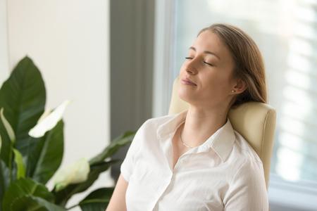 Ruhiges attraktives Frauengefühl entspannt im Bürohaus, die ruhige aufmerksame Geschäftsfrau, die zurück auf Stuhl mit den geschlossenen Augen, meditierend bei der Arbeit sich lehnt, tief einatmet, um sich zu entspannen, kein Druck am Arbeitsplatz