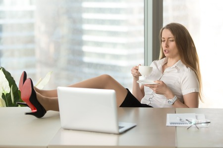 Relaxed businesswoman feels too lazy avoiding work, secretary behaves inappropriately, drinks coffee with feet on desk at workplace, looks at laptop, shows bad manners at office, employee misconduct