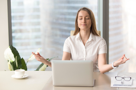 Mindful businesswoman practices breathing exercises at workplace, peaceful woman enjoys yoga with eyes closed at desk, no stress, keep calm, hands in chin mudra gesture, office meditation, portrait