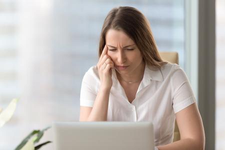 La donna di affari di Shortsighted che strabica gli occhi che esaminano lo schermo del computer portatile del pc mentre si siedono a casa l'ufficio, stanco della donna premurosa del computer che ha vista debole debole, cattiva vista, visione confusa, ha bisogno dei vetri Archivio Fotografico - 83788266
