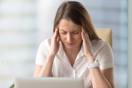 Migraña en el trabajo Infeliz empresaria sufre de fuerte dolor de cabeza crónico, tocando las sienes con los ojos cerrados, deprimido sentimiento de dolor de la señora, mujer estresada trata de calmarse, disparo de la cabeza