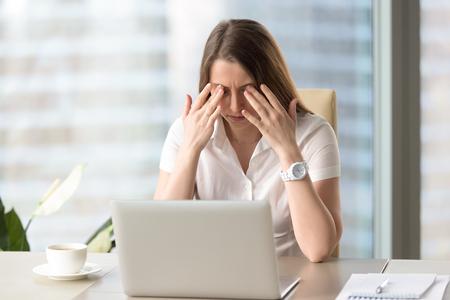 Junge Geschäftsfrau, die Übungen am Arbeitsplatz tut, um müde von den Computeraugen zu entlasten, massierte geschlossene Augenlider, um Muskeln zu entspannen, Spannung zu verringern, Vision zu verbessern, Yoga für Augenbelastung, Augenlichtentspannung Standard-Bild