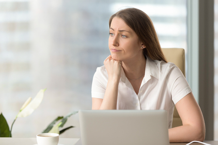Discontented thoughtful woman with hand under chin bored at work, looking away sitting near laptop, demotivated office worker feels lack of inspiration, no motivation, boring routine, creative crisis