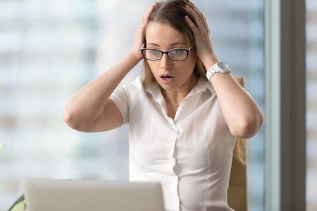 ラップトップ pc を見て驚いて実業家驚いてショックを受けた顔をして女性と手、突然コンピューターが予期せずクラッシュ、衝撃的なニュース、致
