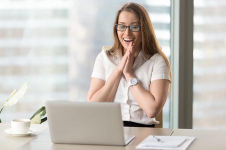 Gelukkige onderneemster die met vreugde op het werk lachen, die gelukkig het laptop scherm bekijken, die opgewekt over online winst voelen, die op grappige video op computer letten, die positief goed nieuws in Internet genieten