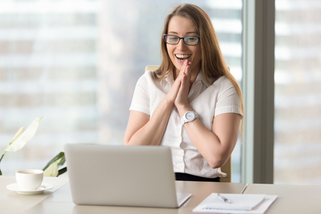 Happy businesswoman laughing with joy at workplace, gladly looking at laptop screen, feeling excited about online win, watching funny video on computer, enjoying positive good news in internet