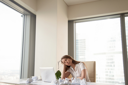 Tired office worker dozing half asleep on hand sitting at desk with laptop and crumpled paper, exhausted unproductive businesswoman needs to finish urgent work, too much paperwork, copy space Stock Photo - 86859085