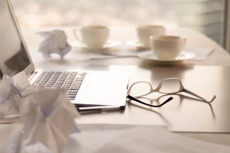 Close-up zijaanzicht van bureau met laptop, koffie, glazen en verfrommeld papier op tafel, zoeken naar nieuwe ideeën concept, rotzooien op de werkplek na vergadering, creativiteit crisis, hard werken zonder oplossing