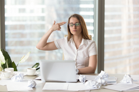 Overwhelmed tired businesswoman puts finger gun to head, overworked with too much paperwork, hardworking employee kills herself by gesture, exhausted overload by lot of work, needs help, hates job
