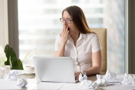 Moe overwerkte slaperige zakenvrouw gapende zit aan bureau met laptop en verfrommeld papier, gapende vrouw voelt gebrek aan slaap of chronische vermoeidheid werkt laat na uur, te veel papierwerk