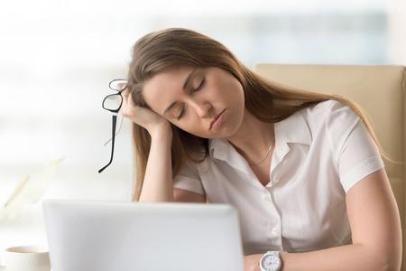 Gelangweilte schläfrige Geschäftsfrau, die halb am Arbeitsplatz schläft, faule Frau desinteressiert an der langweiligen Routine, müder Angestellter, der auf Hand während der Pause döst, einschlafen am Schreibtisch, Schlafmangel, Hauptschuß