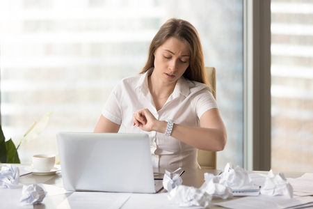 Busy punctual businesswoman checking time to deadline, looking at wristwatch while working with laptop and documents, need to finish work on time, counting on overtime bonus, waiting workday ending