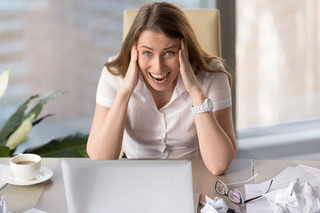Stressed businesswoman screaming in hysterics, holding head in hands, exhausted employee feeling desperate about problems, overwhelming stress, unable to cope with nervous breakdown, burnout at work