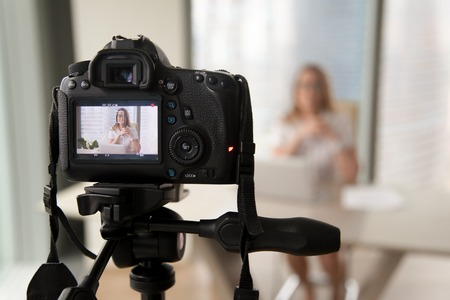 Professional digital equipment recording video blog of businesswoman, online business coach making presentation for website, filming popular vlog or master class for videoblog channel, focus on camera Stockfoto