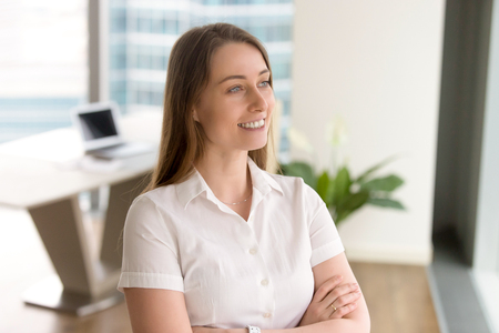 Head shot portrait of ambitious businesswoman with arms crossed looking forward to future, attractive confident career woman enjoying success and business perspectives while standing in office Stock Photo