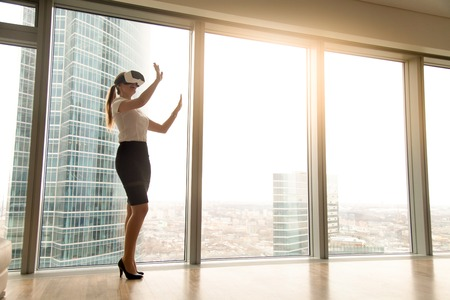 Excited smiling businesswoman wearing virtual reality glasses, happy woman exploring augmented world, interacting with digital interface while standing near big window of modern office, copy space