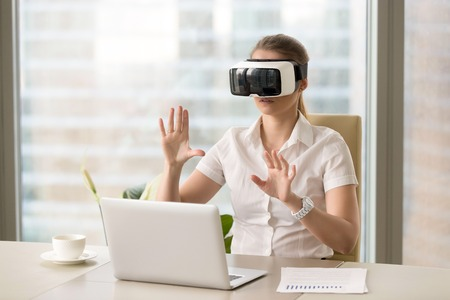 VR headset in use, businesswoman wearing virtual reality glasses for laptop and gesturing sitting at office desk, working with augmented reality apps, future computer technology for business concept Stock Photo