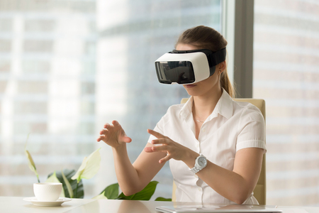 VR headset for business experience, curious woman wearing goggles touching 3d virtual objects seem like real, young businesswoman exploring augmented reality simulation with hands, try before you buy