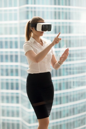 Serious businesswoman in VR headset trying virtual reality 3d tour, interacting with virtual interface to make conference call, watching 360 degrees video, future technology for business, vertical