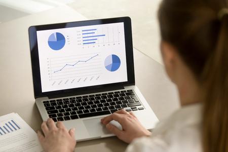 컴퓨터에서 작업하는 사업가에서 후면보기 프로젝트 통계 분석 노트북 화면, 회사 성장, 애플 리 케이 션업 소프트웨어에 대 한 그래픽 정보에 대 한