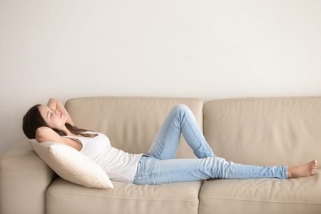 Young woman lying on couch cushion with eyes closed, relaxing on cozy sofa pillow, relaxed girl taking nap at home hands behind head, breathing fresh air, no stress, enjoying day off in living room Banque d'images