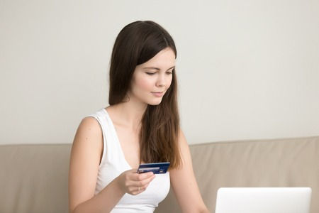 Young lady shopping on internet sitting at home with laptop computer, pretty girl paying for services by credit card, making secure online payment, purchases goods in web store, checking bank account Stock Photo - 83950252