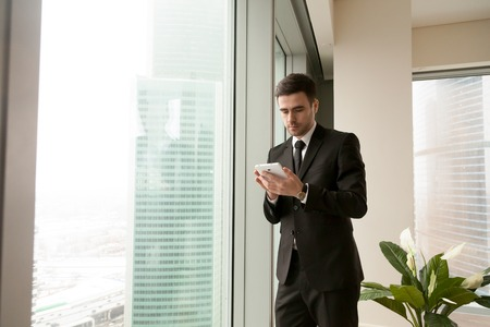 Serious businessman holding tablet standing near big office window, using business apps for organizing meetings, making payments, planning daily tasks, reading news, monitoring realtime market data Stock Photo
