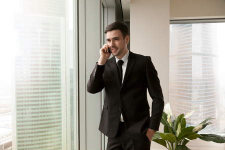 Young happy businessman talking on cell standing near big office window, executive making answering call, consulting clients by smartphone, phone negotiations, unlimited mobile tariff, cheap roaming