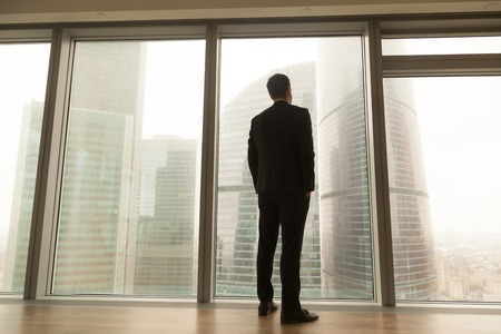 Contemplative businessman standing near big window looking out at city, thoughtful entrepreneur building future plans, thinking over ways to overcome business problems, pass through crisis, back view Imagens