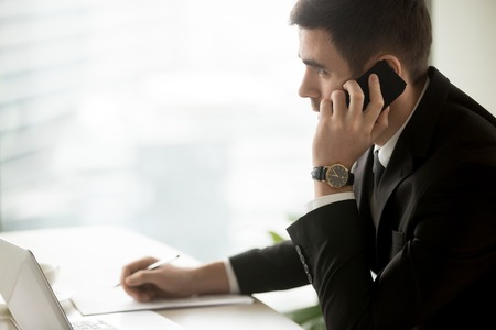 Serious businessman talking on cell sitting at office desk, executive manager answering call, consulting clients by mobile, making arrangements, successful phone negotiations, side view, copy space