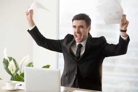 Excited businessman celebrating unbelievable business success, raising hands holding papers with rising financial graphs, screaming with joy, gained large profit, got big money, successful investment