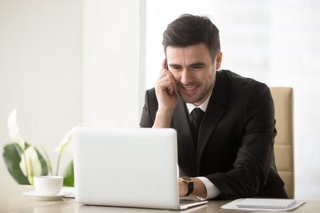 Glimlachende zaken man praten op mobiele telefoon zit op kantoor voor laptop, met succesvolle mobiele onderhandelingen met klant, manager consulting klant telefonisch, gemakkelijk internet bankieren