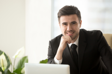 Portrait of smiling attractive consultant wearing suit posing with laptop, happy businessman working on computer, successful online business owner, stock trader or coach looking at camera, headshot Stockfoto