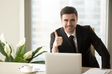 Bem sucedido empresário confiante, olhando para a câmera, mostrando os polegares para cima ou como sentado na mesa do escritório, soluções eficazes, recomendando a melhor escolha para os negócios, sinal de sucesso, boa ideia, ótimo trabalho