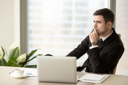 Przemyślany, zamyślony biznesmen odwracający wzrok, siedzący w pobliżu laptopa w miejscu pracy, odnoszący sukcesy przedsiębiorca zastanawiający się nad nowymi sposobami usprawnienia biznesu, perspektywami na przyszłość, zarządzaniem ryzykiem