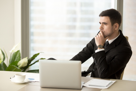 Thoughtful pensive businessman deep in thoughts looking away sitting near laptop at workplace, successful entrepreneur thinking over new ways to improve business, future perspectives, managing risks Stock Photo