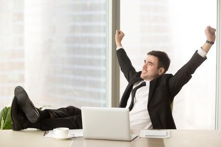 사무실에서 노트북으로 작업을 완료 만족 된 사업가 손을 제기 하 고 주말 휴가, 편안한 근무일의 기대에 열심히 일 후 편안한 테이블에 발을 박 았, 편