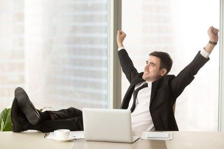 Satisfied businessman happy to finish work with laptop at office, raises hands and puts feet up on table, relaxing after hard working day in expectation of weekend leave, relaxed workday, no stress Zdjęcie Seryjne